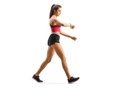 Full length profile shot of a fit young woman walking checking her sports arm-band isolated on white background