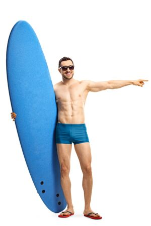 Full length portrait of a man in swimwear wearing sunglasses holding a surfing board and pointing to the side isolated on white background