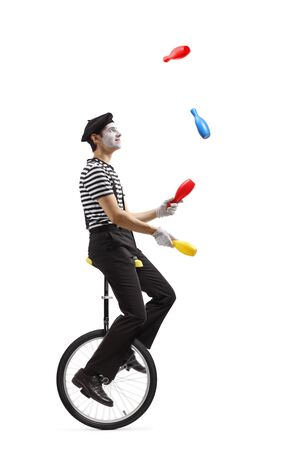 Full length profile shot of a pantomime guy riding a mono-cycle and juggling isolated on white background