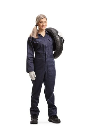 Full length portrait of a female auto mechanic holding a tire isolated on white background