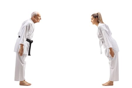 Full length profile shot of a young woman bowing to a senior karate master isolated on white background