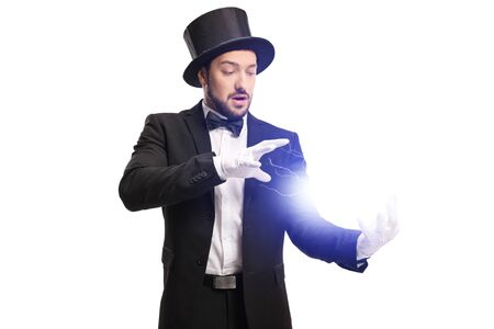 Magician performing a trick with electricity with his hands isolated on white background