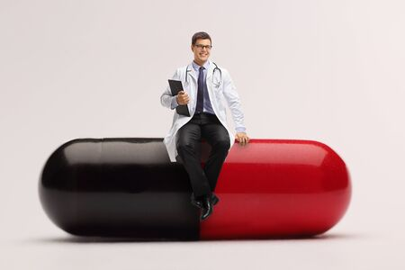 Young male doctor sitting on a big pill isolated on white background Фото со стока