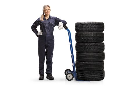 Full length portrait of a female auto mechanic standing with a pile of tires on a hand-truck isolated on white background
