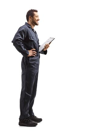 Full length profile shot of a male worker in a uniform holding a clipboard with a document isolated on white background