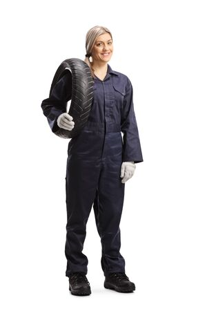 Full length portrait of a female auto mechanic holding a car tire isolated on white background