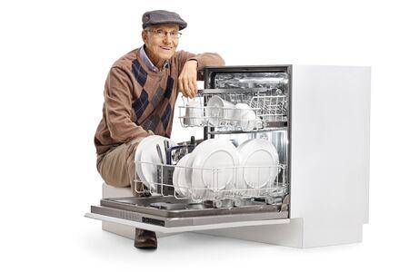 Elderly man kneeling next to a full dishwasher machine isolated on white background Foto de archivo