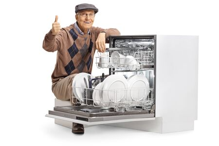 Elderly man kneeling next to a full dishwasher machine and showing thumbs up isolated on white background