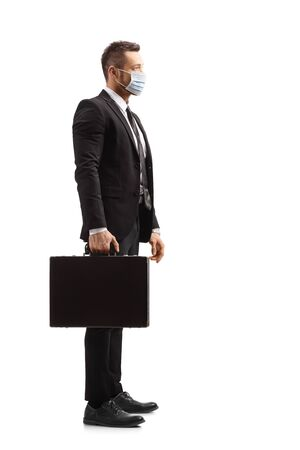 A young businessman holding a briefcase and wearing a face mask isolated on white