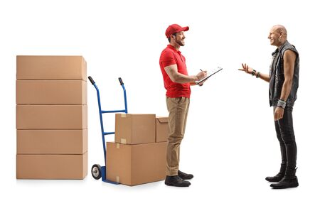 Full length shot of a delivery guy delivering boxes to a bald punk man isolated on white Stockfoto