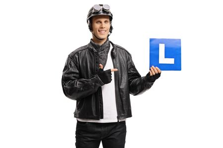 Young man biker holding a drivers learning plate and pointing isolated on white background