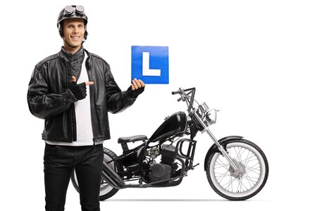Biker holding a drivers learning plate and standing next to a chopper motorbike isolated on white background
