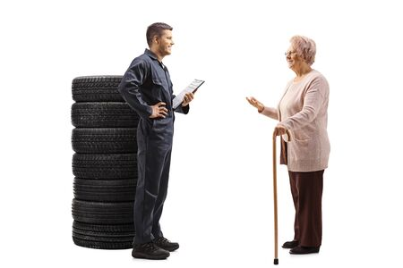 Full length profile shot of an elderly woman talking to an auto mechanic isolated on white background