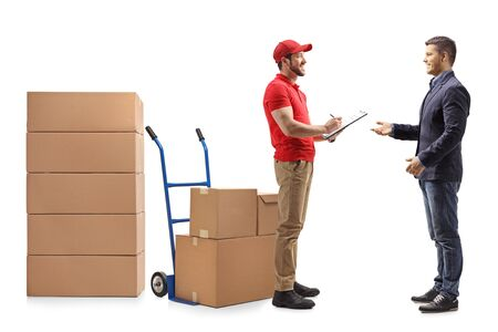 Full length shot of a delivery man with a document handing boxes to a man isolated on white background