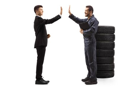 Full length profile shot of a young man in a suit gesturing high-five with an auto mechanic worker isolated on white background