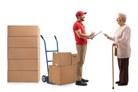 Full length shot of a delivery guy writing a document and delivering boxes to an elderly woman isolated on white background