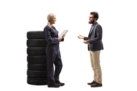 Full length profile shot of a female auto mechanic talking to a male customer isolated on white background