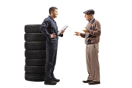 Full length profile shot of an auto mechanic and an elderly man talking isolated on white background