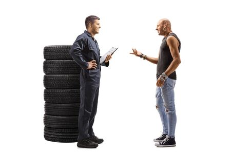 Full length profile shot of an auto mechanic and a male customer talking isolated on white background