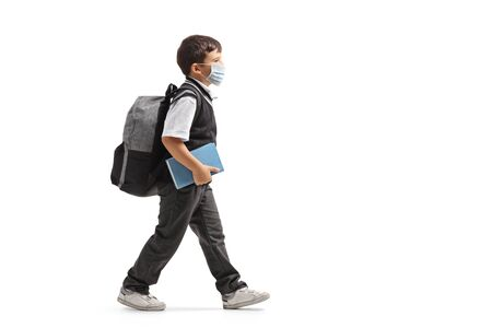 Full length profile shot of a schoolboy with a backpack walking and wearing a protective face mask isolated on white background Standard-Bild