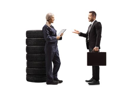 Full length profile shot of a woman auto mechanic worker talking with a businessman isolated on white background