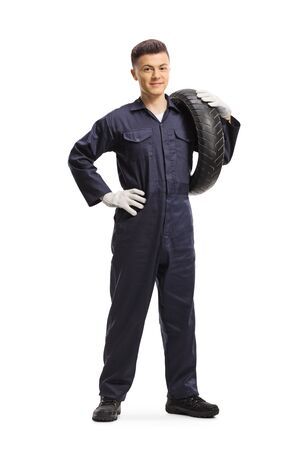 Full length portrait of a mechanic carrying a motorbike tire and smiling at the camera isolated on white background