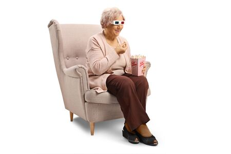Elderly woman with 3d glasses sitting in an armchair eating popcorn isolated on white background