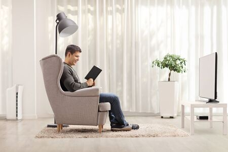 Profile shot of a man reading a book and sitting in an armchair in a living room