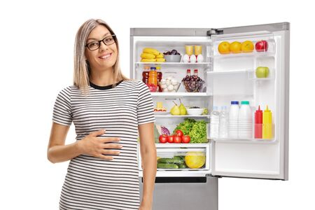 Young woman holding his hand on his stomach in front of a full refrigerator isolated on white background