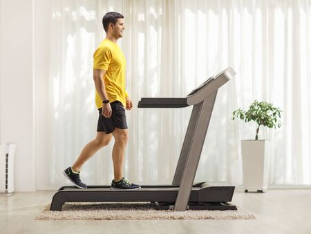 Full length profile shot of a young man walking on a treadmill at home