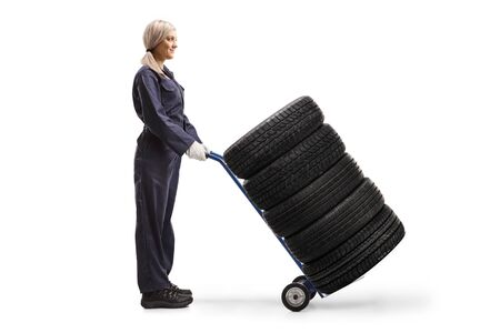Full length profile shot of a female auto mechanic standing with tires on a hand-truck isolated on white background Stockfoto