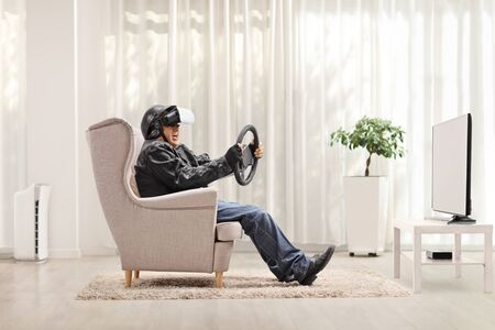 Elderly man in an armchair using a VR headset and holding a steering wheel in front of a tv