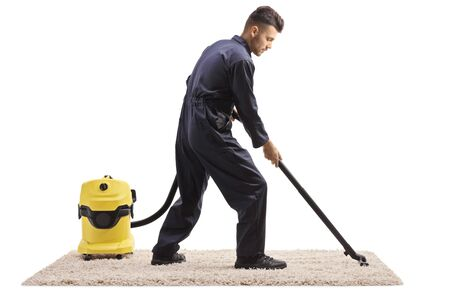 Full length shot of a male worker in a uniform with a vacuum cleaner hoovering a carpet isolated on white background Imagens