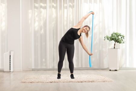 Full length portrait of a woman exercising with an elastic band at home Stock Photo