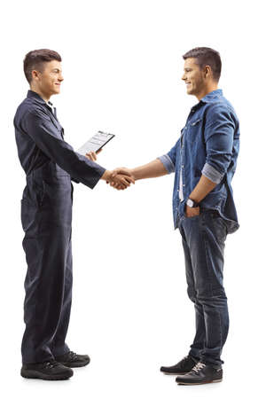 Full length profile shot of a young mechanic shaking hands with a casual man isolated on white background