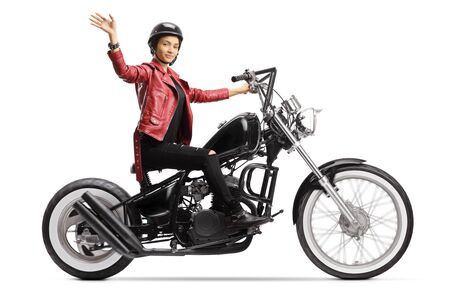 Young woman biker with a helmet and a leather jacket riding a chopper and waving isolated on white background Stok Fotoğraf