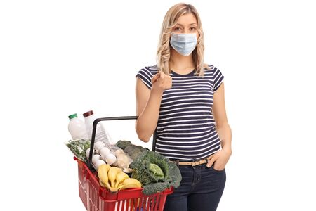 Young woman wearing a protective face mask and carrying a shopping basket isolated on white background