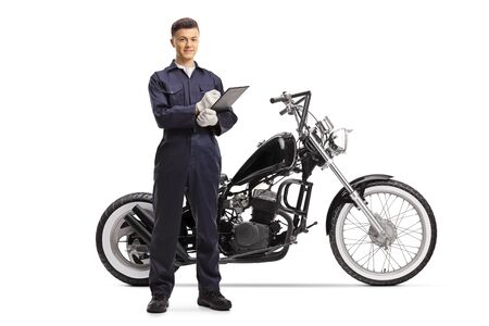 Full length portrait of a motorcycle mechanic with a chopper standing and writing on a clipboard isolated on white background
