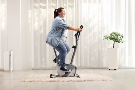 Young overweight woman riding an exercise bike at home Stok Fotoğraf