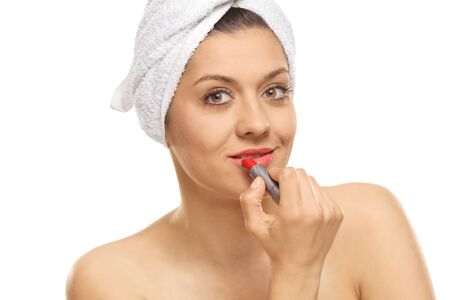 Woman with a towel on her head putting red lipstick isolated on white background