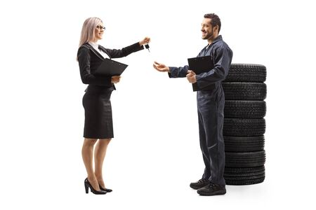 Full length profile shot of a businesswoman giving car keys to an auto mechanic standing next to a pile of tires isolated on white background 写真素材