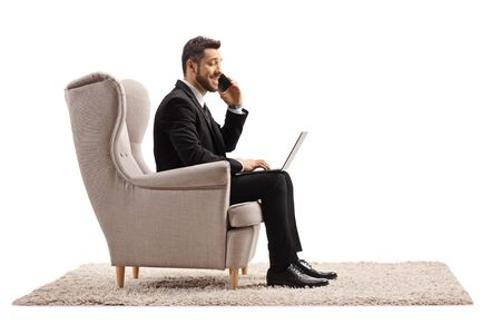 Businessman working from home on a laptop computer and talking on a mobile phone isolated on white background