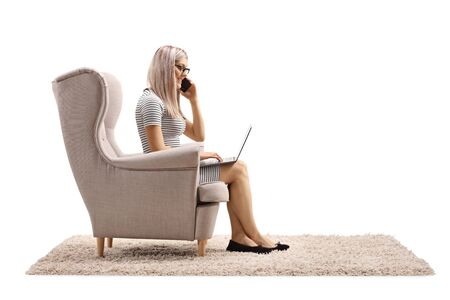 Woman sitting in an armchair and working from home on a laptop computer while talking on a phone isolated on white background