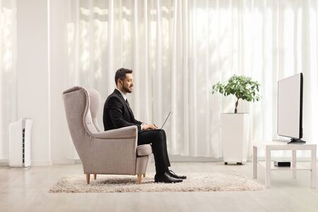Businessman in an armchair working from home on a laptop computer
