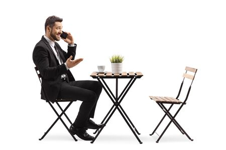 Full length profile shot of a businessman in a cafe talking on a mobile phone isolated on white background Banque d'images