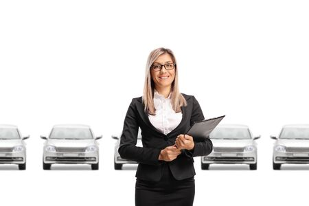 Car saleswoman holding a clipboard with a document in front of a row of silver cars isolated on white background Stock fotó