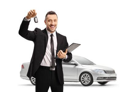 Man in a suit holding a car key and posing in front of a brand new silver car isolated on white background Stockfoto