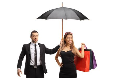 Man in a suit holding an umbrella over a young woman with shopping bags isolated on white background