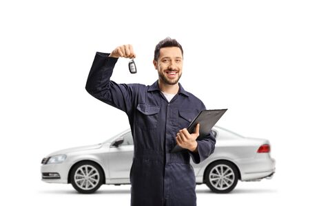 Auto mechanic holding a clipboard with documents and car key and posing with a silver car isolated on white background