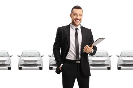 Car dealer holding a clipboard with documents and standing in front of silver cars isolated on white background